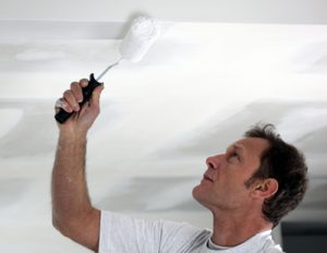 A professional painting contractor uses a rolling brush to paint a ceiling white