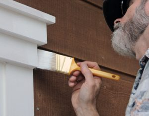 Professional painter carefully painting the window trim on a house