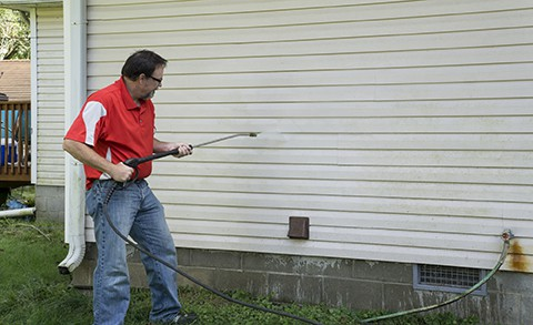Contractor using a high pressure washer to remover algae and mold from a house with vinyl siding.