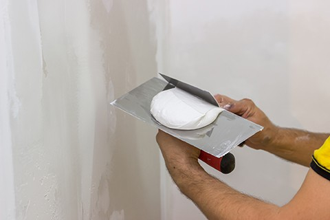 Mixing skimming plaster on trowel for the patching